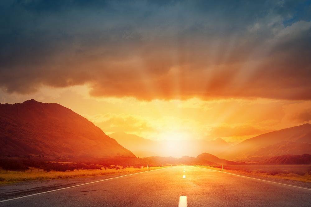 Empty asphalt road and sun rising at skyline.jpeg