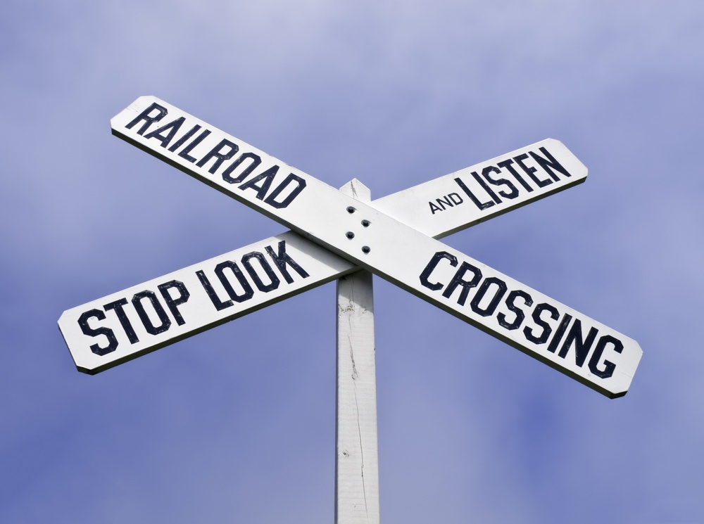 Railroad crossing sign with warning to stop, look, and listen